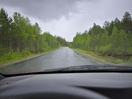 激しい雨に濡れて滑りやすい路面から田舎の高速道路を運転します。ワイパー アクション、ドライバーのビューで。
