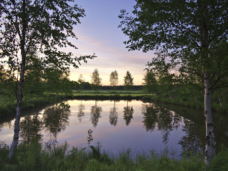 Beautiful scene by a small pond in midsummer night in Finland.