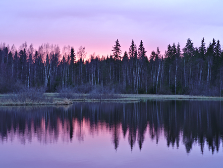 Beautiful red sky over forest and lake at time of sunset. Natural background. Stock Photo