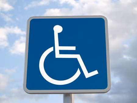Standard disabled sign with clouds in the background photo