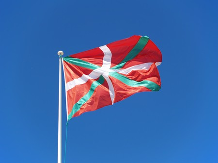 fluttering: Basque Flag fluttering in blue cloudy sky Stock Photo