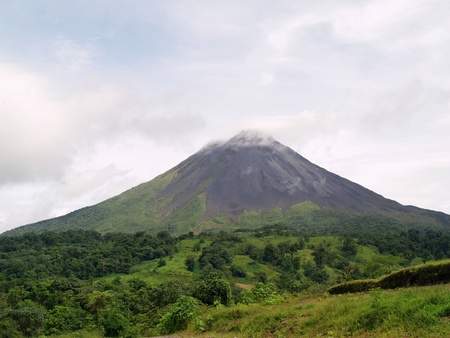 coming out: Arenal volcano in Costa Rica on a clear day. Smoke & steam coming out from the top cone Stock Photo