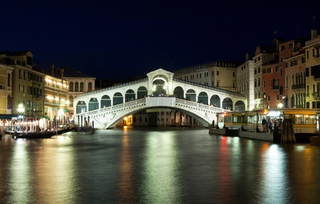 VENICE, ITALY - JULY 02: Tourist enjoy day and night on the Rialto Bridge on July 02, 2011 in Venice, Italy. Originally built out of wood and having collapsed, in 1591 was completed out of stone.  Stock Photo - 12368267