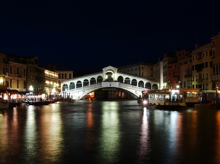VENICE, ITALY - JULY 02: Tourist enjoy day and night on the Rialto Bridge on July 02, 2011 in Venice, Italy. Originally built out of wood and having collapsed, in 1591 was completed out of stone.