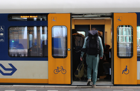 Utrecht, the Netherlands, February 15, 2019: A traveller with backback catching a train (sprinter) in the netherlands