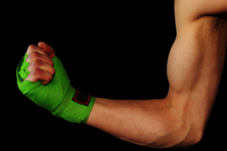 Male showing biceps with green boxing straps Reklamní fotografie