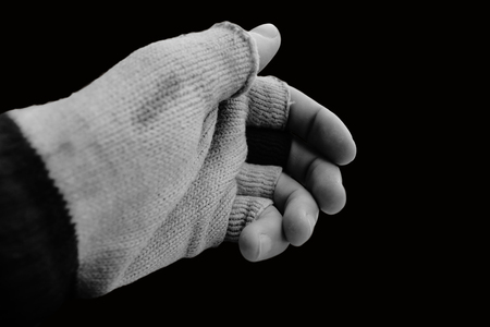 Hand with old glove that lacks the finger-tops on a black background and in black and white