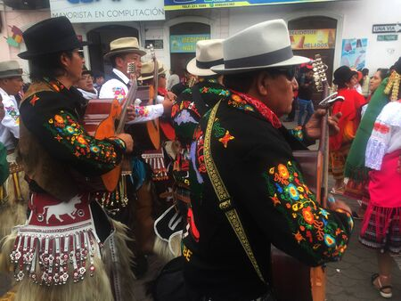 Otavalo, Ecuador: 29-6-2019: Festival with colorful indigenous man making music on the streets in the sierra of ecuador Sajtókép
