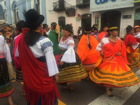 Otavalo, Ecuador: 29-6-2019: Festival with colorful indigenous woman dancing on the streets in the sierra of ecuador
