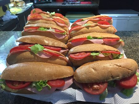 A batch of sandwiches filled with ham, tomatoes and lettuce ready to be sold