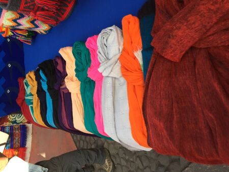 Different scarfs in several colors and textiles for sale at a market stand of Otavalo, ecuador Stockfoto