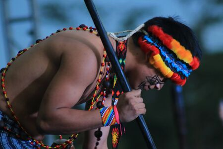 Puyo, Ecuador, 17-8-2019: An indigenous tribe called shuar performing their dance in traditional clothing and spears