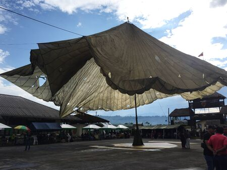A large army parachute hung up as a tent to provide shade and cover on a festival