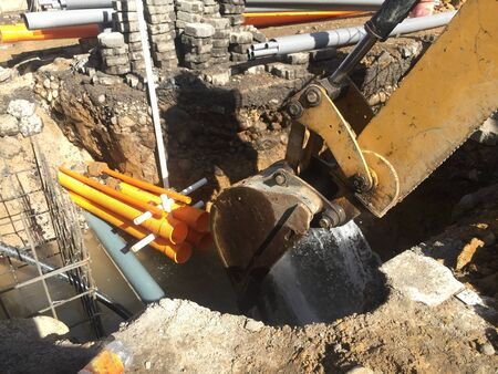 Excavator is being used to stop the water after breaking a waterpipe during construction work