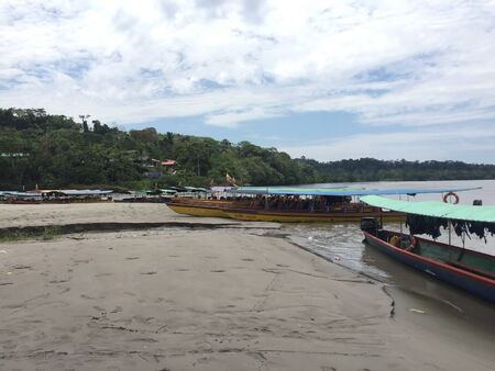 Tena, Ecuador - 29-9-2019: elongated canoes used to guide tourist over a large tropical river