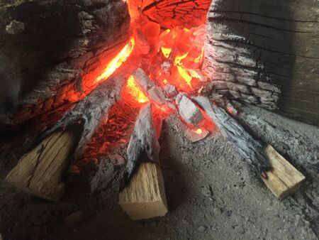 Three wooden sticks halfway burned laying just outside the glowing coals of a fire