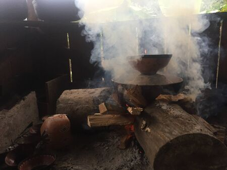 Native amazonian method of pottery: clay mockawas or bowls are being baked in ash on a fire