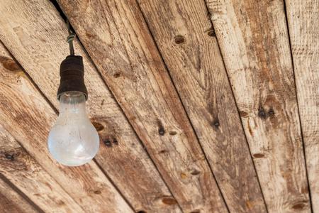 enchufe de luz: Nonfunctional Classic Light Bulb in an Old Socket to E27 Light Bulbs on Wooden Ceiling Foto de archivo