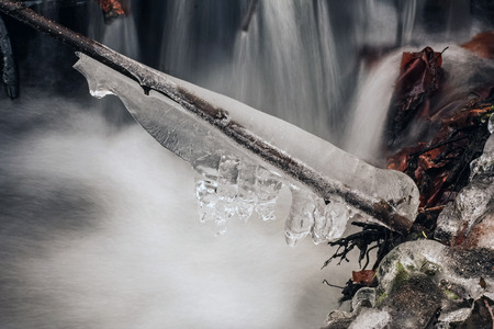 frozen creek: Frozen Water Ice on a Branch above the Creek in Springtime Stock Photo