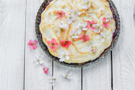 whites: Top View on Fruit Pie with Flowers and Whipped Egg Whites on a Wood Table