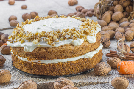walnut cake: Carrot and Walnut Cake Topped with Cream  on Jute Background with Walnuts, Cinnamon and Carrots