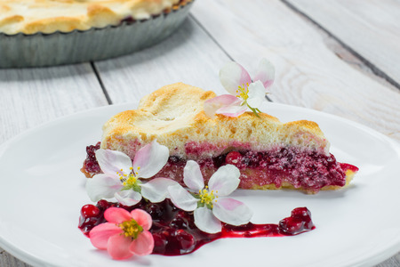 Slice of Fruit Pie with Flowers and Currant-Blueberry Jam on a plate