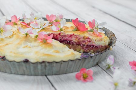 Cut Fruit Pie with Flowers and Whipped Egg Whites on Wood Table
