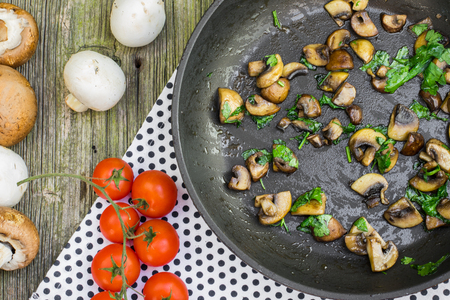 sautee: Top View on a Saut?ed Brown and White Champignon Mushrooms with Parsley on Pan on Old Wooden Table