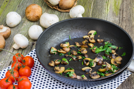 sautee: Saut?ed Brown and White Champignon Mushrooms with Parsley on Pan with Tomatoes on Old Wooden Table