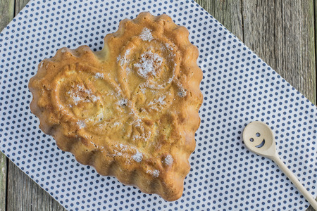 walnut cake: Top view on raisin walnut cake in the shape of a heart with wooden smiley spoon Stock Photo