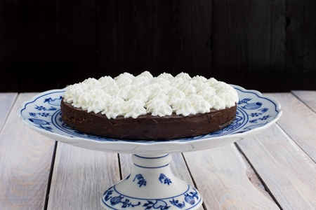 flourless chocolate cake: Low height dark chocolate cake with whipped cream on a Blue Onion Plate