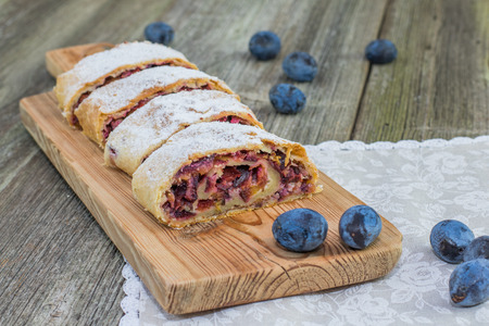 Plum strudel on wood plank timber with fresh plums on a old wooden board Stock Photo