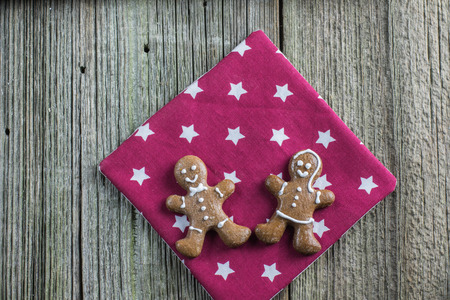 Top View on two christmas gingerbread mens on violet placemats with white stars