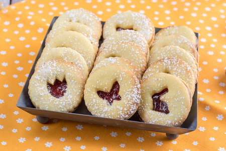 Detailed Linzer Easter cookies with a strawberry jam, dusted with sugar arranged on tin tray on orange clothtable