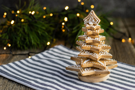Gingerbread christmas tree with Christmas lights on wooden table