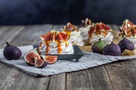 Meringue figs with whipped cream and caremel glaze on black tray Stock Photo