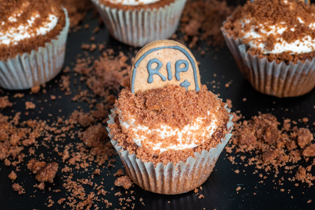 Detail on a Cocoa Banana Halloween cupcakes with tombstone on black background Stock Photo