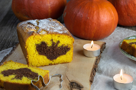 Detail on a Halloween Pumpkin cake with a cocoa bat symbol on the cut with tea candles Stock Photo