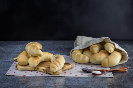 Homemade Traditional Czech pastry - white bread roll (rohlik) with salt and poppy seeds on a wooden board Stock Photo