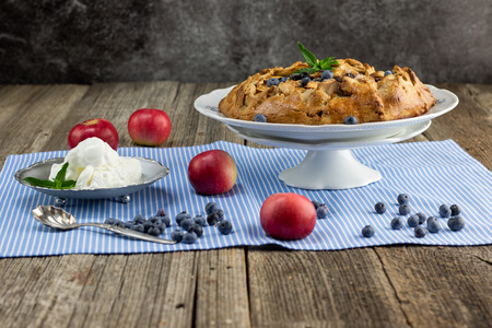 Rustical apple pie with blueberry, mint leaf and vanilla ice cream