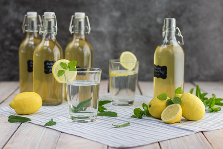 Homemade mint syrup and glass with lemonade from a syrup with lemon slice