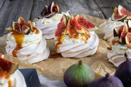 Small figs pavlova with whipped cream and caremel glaze on baking paper Stock Photo