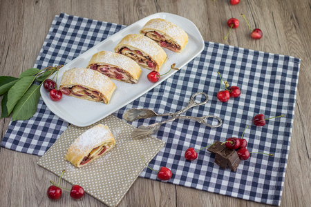 Top view on a sliced Cherry chocolate strudel with confectioner pliers Stock Photo