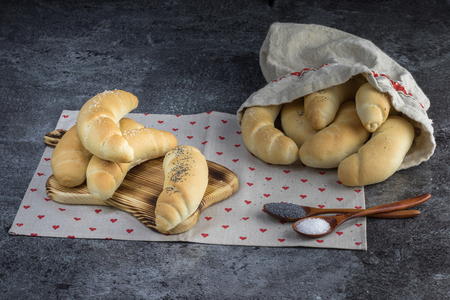 Homemade Traditional Czech pastry - white bread roll (rohlik) with salt and poppy seeds on a wooden board and in a linen bag on a marble background