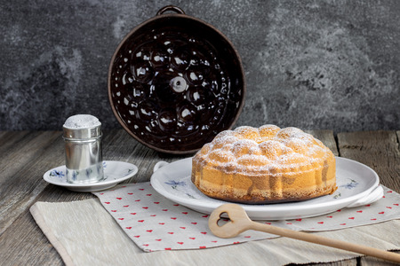 Czech traditional marble bundt cake with sugar bowl on old ceramic dining set