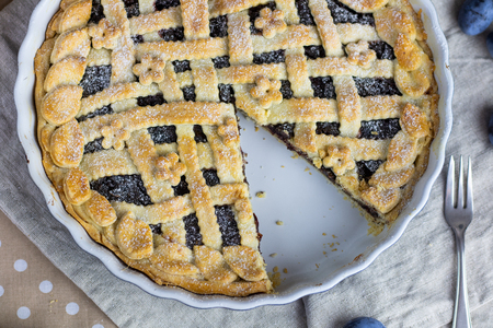 Top view on a sliced Plum and poppy seeds pie in cake form Stock Photo