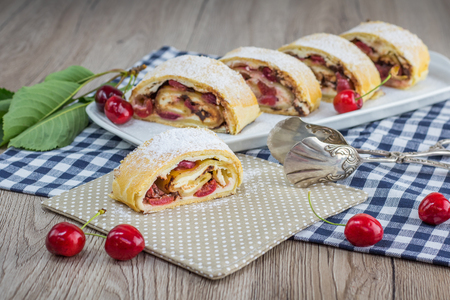 Sliced Cherry chocolate strudel with confectioner pliers