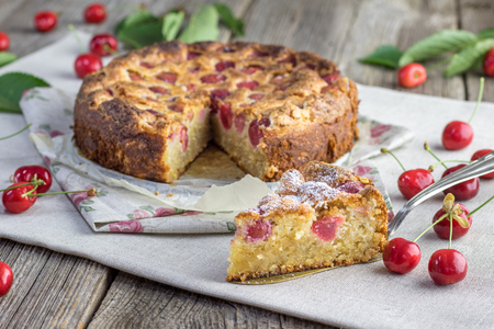 Piece of Czech rounded black cherries bubble cake or souffle on table