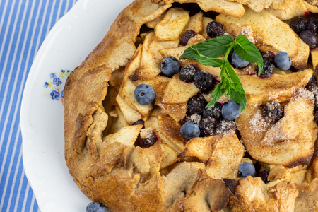 Detailed top view on a Rustical apple pie with blueberry and mint leaf Stock Photo