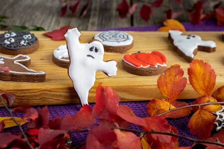Halloween ghost cookies on a wooden board and autumn leaves Stock Photo